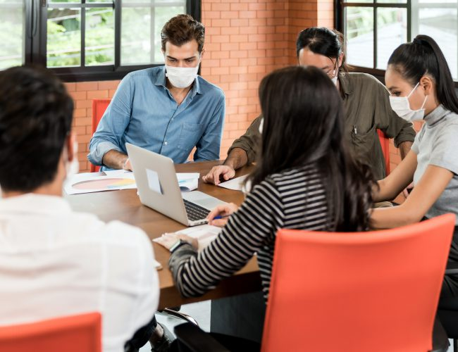 Group of asian and caucasian business person team meeting and brainstorm in meeting room after office reopen, they wear protective face mask as new normal practice to prevent coronavirus infection.